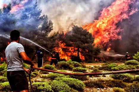 Palomiehet ja vapaaehtoiset taistelivat raivoisaa metsäpaloa vastaan Verorissa Kreikan Peloponnesoksella viime tiistaina. Säiden ääri-ilmiöt yleistyvät ilmastonmuutoksen edetessä.
