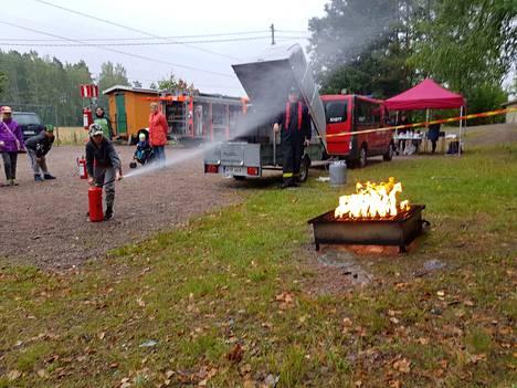 Oskari Koskinen näyttää mallisuorituksen siitä, miten palo sammutetaan jauhesammuttimella.