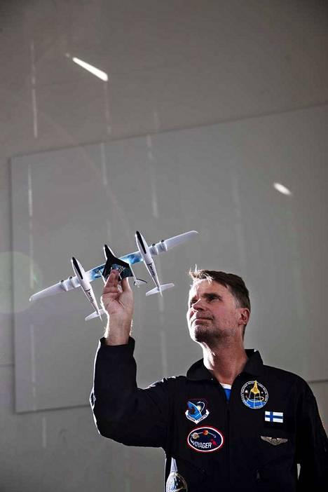 Vesa Heilalan kädessä on pienoismalli Virgin Galactic yhtiön WhiteKnightTwo-emoaluksesta, jolla koneen vatsapuolelle kiinnitetty SpaceShipTwo-avaruusalus kuljetetaan 15 kilometrin korkeuteen. Siellä avaruusalus irtoaa ja se kuljettaa Heilalan avaruuden rajalle sadan kilometrin korkeuteen.