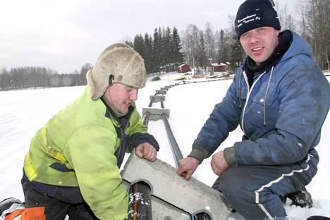 Jukka Melanen ja Tomi Niinilammi asettivat Pohjois-Kuoreveden vesiosuuskunnan vesi- ja viemäriputkiin painoja Kuoreveden kirkon lähellä jäälle vuonna 2008.