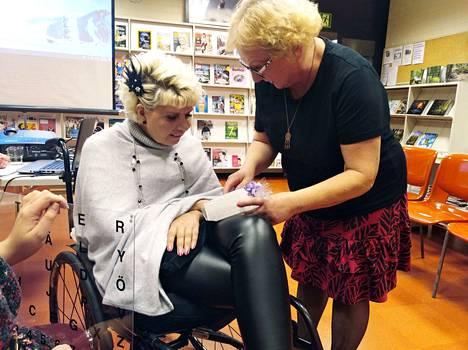 Kirjastovirkailija Maire Riikonen (oik.) ojensi Marja Korhoselle Multian kirjaston lahjan, Kalevan tulen kynttilän, jossa on kunnan muurahaisvaakuna.
