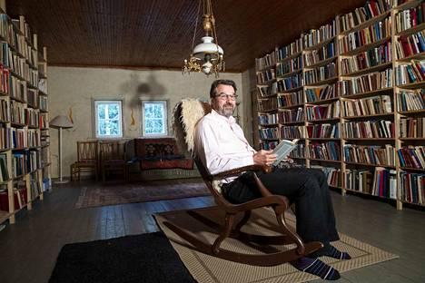 Tomin kirjaston vasen seinä on täynnä tietokirjallisuutta, oikealta löytyvät romaanit. Tomi lukee mieluiten tietokirjallisuutta. Kiikkutuoliinsa hän asettuu kuitenkin Antti Tuurin Rukajärven tie -sotaromaanin kanssa.
