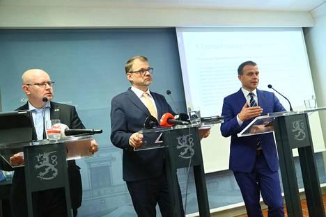 Tiedotustilaisuudessa olivat äänessä työministeri Jari Lindström (sin.), pääministeri Juha Sipilä (kesk.) ja valtiovarainministeri Petteri Orpo (kok.).