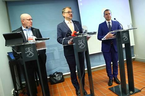 Pääministeri Juha Sipilä (keskellä) esitteli hallituksen ratkaisuehdotusta työministeri Jari Lindströmin ja valtiovarainministeri Petteri Orpon kanssa torstai-iltana.