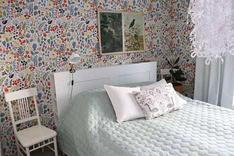 Isäntäparin makuuhuoneessa on ikuinen kesä, sillä sen seiniä koristaa iloisenkirjava Herbarium-tapetti.