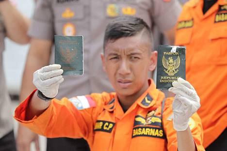 Indonesialainen pelastustyöntekijä näyttää passeja, jotka kuuluvat Indonesian maanantaisessa lentoturmassa menehtyneille. Koneen kyydissä oli 189 ihmistä, ja eloonjääneitä ei ole.