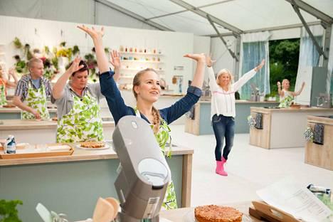Saara, Mari, Tommi ja Sanna nostavat kätensä ylös, kun juontaja Anne Kukkohovi huikkaa, että annettu aika toscapiirakan tekoon on loppunut.
