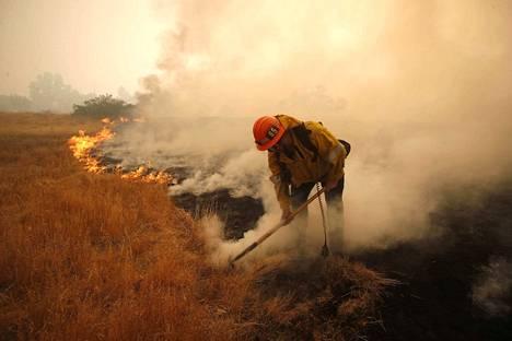 Palomies sammutti maastopaloa Malibussa Kaliforniassa lauantaina. Woolsey fire Malibussa on surmannut kaksi ihmistä.
