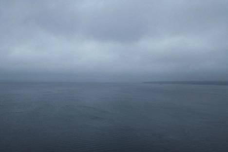 Taivas ja Näsijärvi olivat tasaisen harmaat maanantaina. Hyvällä mielikuvituksella pilviverhon takaa voi aistia häämöttävän valon.