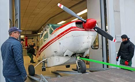 """""""Peltienkeli"""", eli Cessna 206 siirrettiin varovati näyttelytiloihin Mäntän seudun koulutuskeskuksen autohalliin. Paikalla oli Janne Ropposen lisäksi kymmenkunta vapaaehtoista."""
