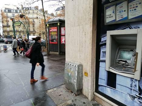 """Protestoijat hajottivat pankkiautomaatin viikko sitten Viktor Hugon aukiolla puolen kilometrin päässä Riemukaaresta. Lehtikioskin kyljessä oleva aikakauslehden kansi povaa viimeisiä päiviä """"ranskalaiselle mallille""""."""