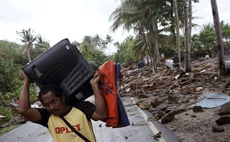 Indonesialainen mies yritti pelastaa, mitä pelastettavissa oli. Indonesiassa on totuttu luonnonkatastrofeihin. Niistä on varoitettu myös suomalaisturisteja.