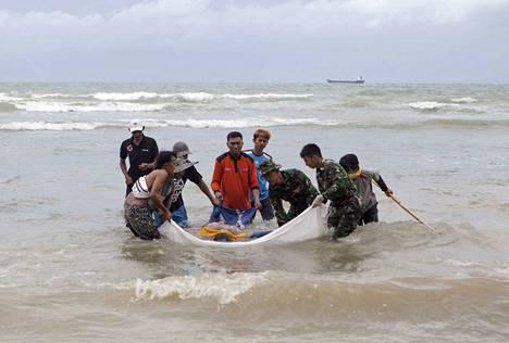 Pelastajat kuljettivat ruumista Anyerin alueella Länsi-Jaavalla.
