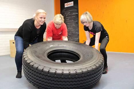 Anne Hakanen näyttää Mervi Hokkaselle ja Raija Virralle, kuinka traktorin rengas soveltuu toiminnalliseen harjoitteluun.