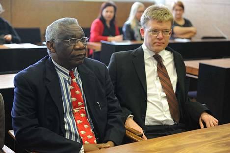 Ruandan kansanmurhasta tuomittu Francois Bazaranban (vas.) on ollut vangittuna vuodesta 2007 lähtien. Hän anoi armahdusta hovioikeudelta, mutta ei saanut. Kun juttua käsiteltiin hovioikeuden valmistelevassa istunnossa vuonna 2011, Bazarambaa avusti Ville Hoikkala.