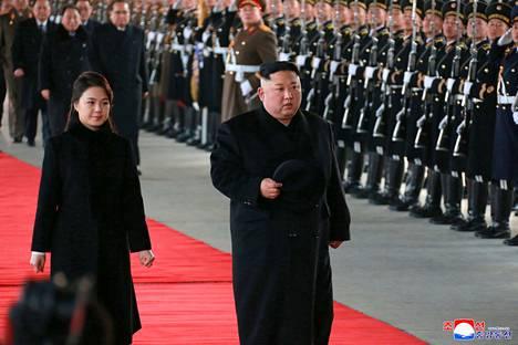 Pohjois-Korean johtaja Kim Jong-un (oik.) ja vaimonsa Ri Sol-ju tarkastivat kunniakomppanian ennen lähtöään kohti Kiinaa maanantaina Pjongjangissa.