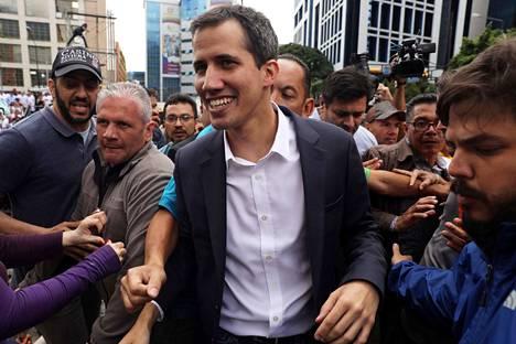 Juan Guaidó tervehti keskiviikkona innostuneita ihmisä Venezuelan pääkaupungissa Caracasissa sen jälkeen, kun oli julistautunut maan presidentiksi.