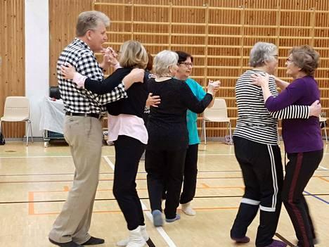Liikuntahallilla tanssitaan levymusiikin tahdissa. Tanssi sujuu myös naisparissa. Myös tunnin vetäjä hakee tanssiin, jotta kenenkään ei tarvitse istua tyhjin toimin.