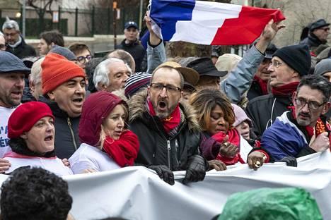 """Laurent Soulié (keskellä) otti osaa sunnuntaina """"punaisten huivien"""" protestimarssille Pariisissa. Protestoijat kajauttivat kansallislaulun La Marseillaisen."""