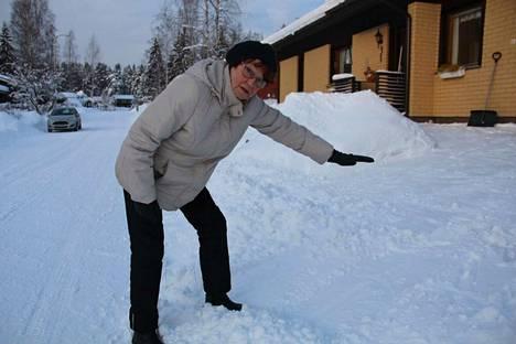 Marja-Leena Järvinen näyttää, mille korkeudelle keskiviikkoinen lumivalli nousi ennen kuin hän sai sen kolattua pois.