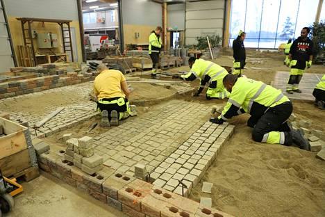 Pihakivien asentajiksi valmistuvat harjoittelevat Kivimiehenkadun hiekkahallissa pohjatöiden tekemistä ja kivien latomista.