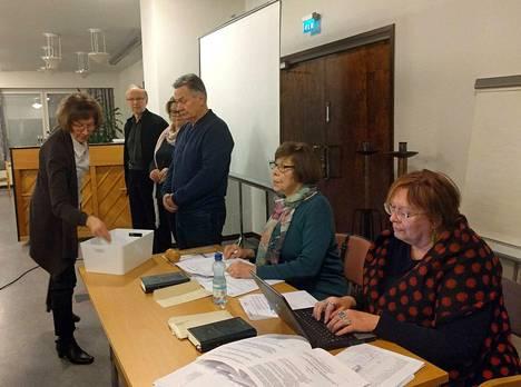 Kirkkovaltuutettu Salme Niska (vas.) kävi antamassa äänestyslippunsa valtuuston puheenjohtajavaalissa viime viikolla. Äänestystä seurasivat talousjohtaja Eija Tuomioja (oik.), puhetta johtanut Ulla Karppila sekä vaalitoimitsijat.