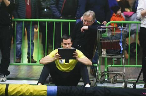 Urho Kujanpää katsoo tietokoneelta, kuinka hyppy on teknisesti sujunut. Valmentaja Raimo Eskola kurkkii valmennettavan olan yli.