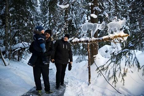 Eino (vas.) ja Henrikki Luoma sekä Paula Perälä olivat Ikurin jääveistospolulla jo kolmatta kertaa. Ilveksiä kuvaava teos pysäytti Tohlopissa asuvan perheen jo suosikkiseurankin takia. – Tämänvuotinen polku on kaikkien aikojen paras, sanoi Perälä.