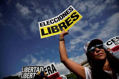 Nainen vaati kyltissään vapaita vaaleja mielenosoituksessa, joka oli järjestetty Venezuelan väliaikaiseksi presidentiksi julistautuneen Juan Guaidón tueksi Panaman pääkaupungissa Panamássa lauantaina.