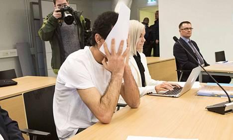 Törkeistä lapseen kohdistuneista seksuaalirikoksista syytetty sai peittää kasvonsa kuvaamisen ajaksi. Vieressään istui hänen avustajansa, asianajaja Ulla-Maija Pöhö.