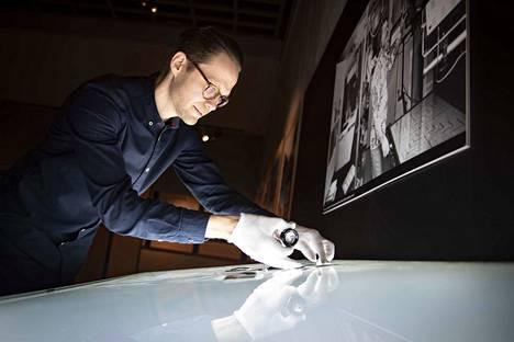 Satakunnan museon amanuenssilla Timo Nordlundilla riittää kiirettä 404 ruutua -näyttelyn rakentamisessa. Valopöydällä museokävijät voivat tutkia Satakunnan Kansan vanhoja negatiiveja.