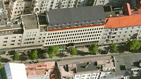 Havainnekuvassa näkyy Hämeenkatu 24:n korotusosa etelän suunnasta. Vuonna 1939 rakennettu Yhdyspankintalo edustaa funktionalismia. Sen oikealla puolella Hämeenkadun ja Kuninkaankadun kulmassa sijaitsee arkkitehti Birger Federleyn suunnittelema jugendtyylinen Kansallispankintalo, jossa toimii nykyään Nordean konttori.
