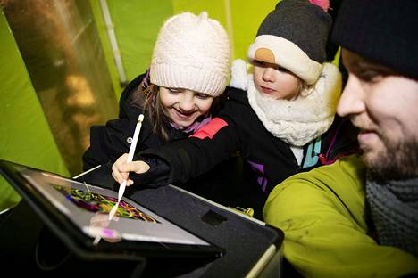 Henni (vas) ja Julianna Holopainen kokeilivat valograffitin tekoa.