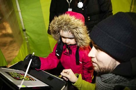 Viisivuotias Aino Lehtonen kirjoitti nimensä. Niko Tiainen opastaa.