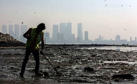 Kaupungin työntekijä puhdistaa Mahimin rantaa Mumbaissa maaliskuun alussa. Raportin mukaan Intian ilmansaasteet tulevat fossiilisten polttoaineiden käytöstä, hiilivoimaloista ja olkien polttamisesta.
