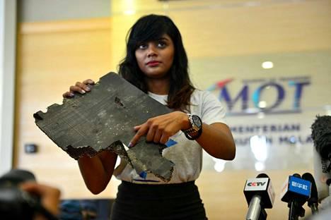 Yhden MH370:n matkustajan omainen pitelemässä palaa, jonka uskotaan kuuluneen turmakoneeseen.