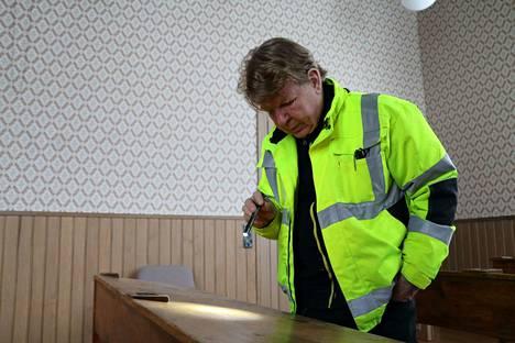 Jokivarren puukoulun entisöinnistä vastaava projektityönjohtaja Ilkka Silén tarkastelee vanhojen pulpettien kirjoituksia.