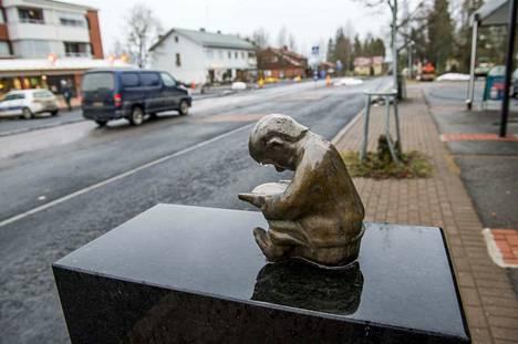 Näkymä Kuhmoisten keskustasta: kylänraitilla, kirjaston edessä on Lukuhetki -patsas.