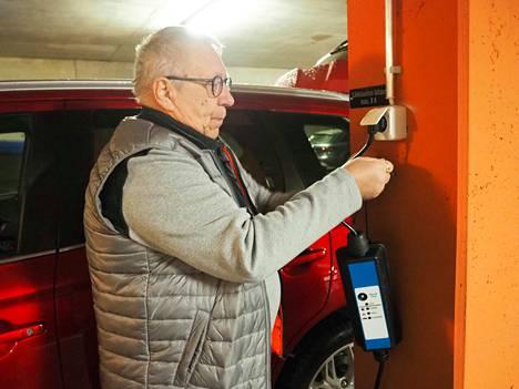 """Mitsubishi-hybridin ajoakku latautuu täyteen yön aikana Jorma Moision kotitalon parkkihallissa Tampereen Härmälänrannassa. Ajossa auto vaihtaa sähkölle heti, kun nopeus laskee alle 65 kilometrin, mutta sähköä voi myös """"säilöä"""" kaupunkiosuuksille."""