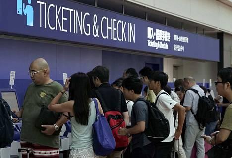 Matkustajat ruuhkauttivat lipunmyyntipisteen Tokion Hanedan lentokentällä torstaina. Länsi-Japania uhkaa voimakas trooppinen myrsky Krosa.