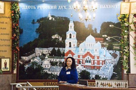 Hotelli Laatokan vastaanotossa työskentelevä Olga Karpova tietää kaiken oleellisen Sortavalan tapahtumista. Kaiken lisäksi hän on kaupunginjohtajan serkku. Taustalla valokuva Valamon luostarista – siitä oikeasta, joka sijaitsee Laatokan saaressa vähän matkan päässä Sortavalasta.