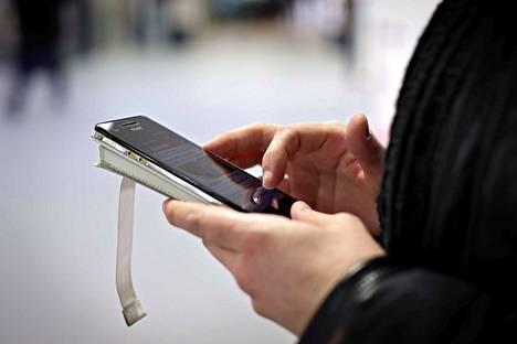 Älypuhelimen käytöstä kuvituskuvaa.