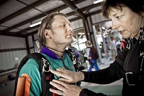 Valokuva Anne Urrilasta (oikealla) vuodelta 2012 Satakunnan Kansasta. Hyppymestari auttaa oppilas Janne Juslinia varusteiden tarkastuksessa laskuvarjohyppykeskuksesa Floridassa.