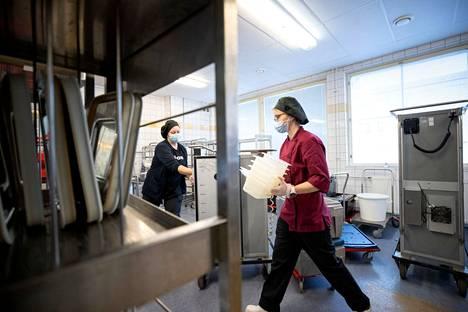 Cygnaeuksen ruokapalvelukeskuksen ruokapalvelutyöntekijät Elina Ahonen (vas.) ja Mona Grönman purkivat perjantaina pesuun päiväkodeista tulleita astioita. Ensi viikolla ruokapalvelukeskuksessa pakataan yläkoululaisille seitsemän päivän ruoat ja kuljetetaan kouluille.