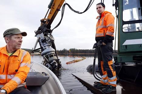 Jukka Lehtikangas souti kuulemaan, miten hänen mökkijärvensä siivous etenee. Imuruoppaajaa käyttää  S-H Servicen Marko Tervamäki.