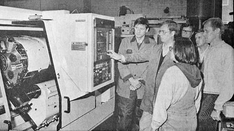 Metallilinjan opettajat Matti Salmi (vasemmalla) ja oikealla olevat Jouko Sahi ja Ulla Lahtinen saivat 1. lokakuuta 1991 opastusta Hannu Vesamäeltä 800000 markan arvoisen uusimman CNC- eli tietokoneavusteisen työstökoneen käyttöön. Taustalla rehtori Hannu Mäkinen ja apulaisrehtori Allan Romanainen seuraamassa opetusta.