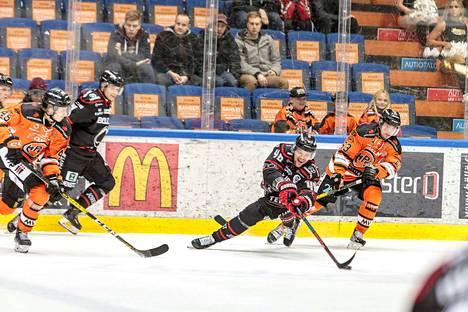 Ässien Mikko Salmiolla oli vaikeuksia pysyä pystyssä HPK-pelaajien vyöryessä niskaan.