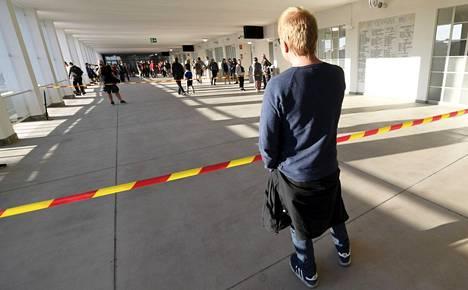 Miehet puhuvat toisilleen matkapuhelimilla koronajärjestelyiden takia erotetuista katsomo-osioista erätauolla jalkapallo-ottelussa Olympiastadionilla viime vuoden elokuussa. Pääkaupunkiseudulla yleisötilaisuuksiin on ensi viikolla tulossa taas tiukempia rajoituksia.