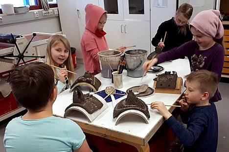 Kuvataide- ja käsityökoulu Emilin oppilaat muotoilevat savesta eläinnaamioita.