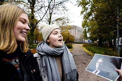 Alma McCracken ja Olivia Timisjärvi arvuuttelivat, kuka kuvassa on. Taustalla näkyy eduskuntatalo.